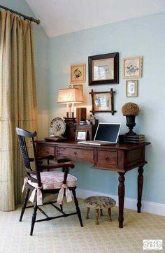 Polgári enteriőr. Tört fehér világos falak, natúr egy színű függönnyel. Női kicsi íróasztalesztergált lábakkal, Ónémetreneszánsz stílusban, előtte hasonló stílusú székkel. pici lábzsámollyal. Sok apró tárgy vaz az asztalon, és a falon több különböző képpel. rajzokkal. At asztalon egy hangulatos lámpa van elhelyezve.