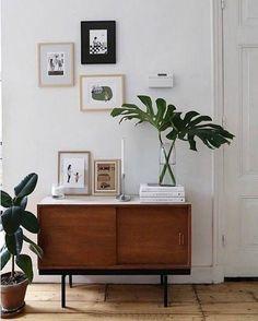 Modern szobarészlet, síma vonalú alacsony szekrény tolóajtóval, natúr diófurníros felületekkel,fekete vékony lábakkal. Tetején fehér síma terítő, szellősen elhelyezett képekkel és szobanövénnyel. A falat is néhány ötletszerűen elhelyezett kép van.