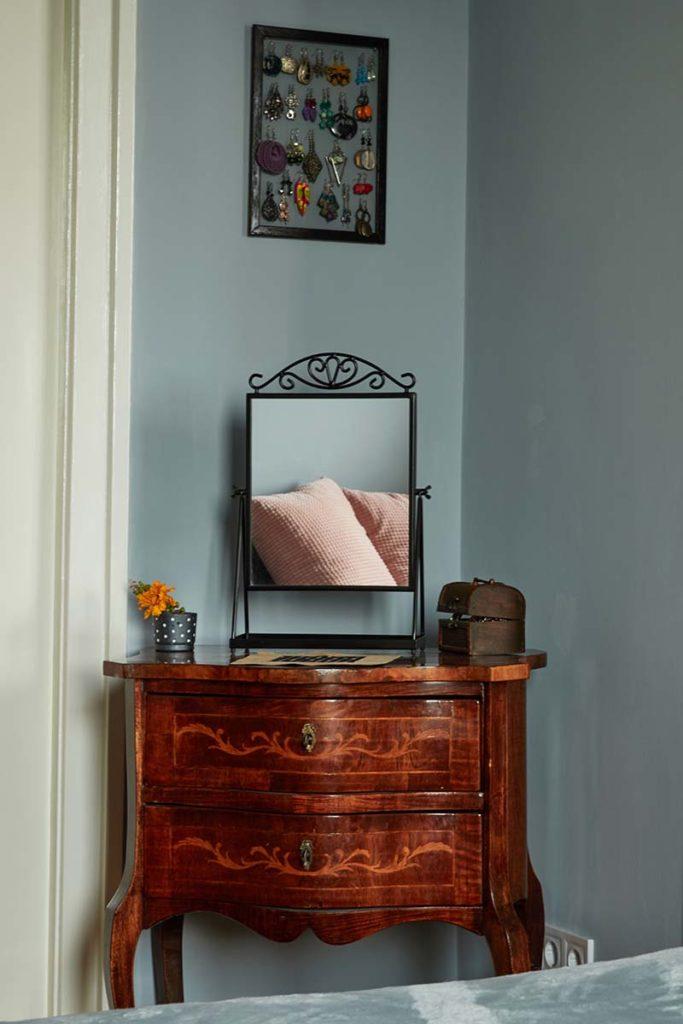 Egy antik smizett (fiókos szekrény) látszik szemben a sarokban, amin egy tükör van elhelyezve, így a halványszürke  falak és az ágytakaró, és rózsaszínű díszpárnák tükröződnek benne. Kedves, harmonikus látvány.