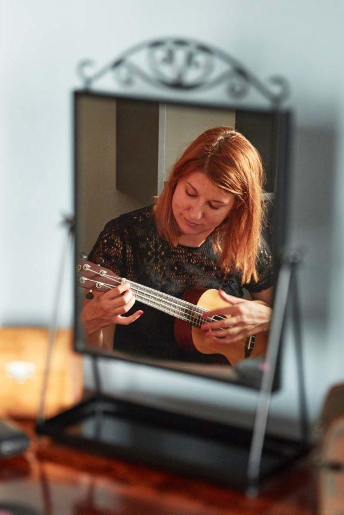 A képen a smizetten álló tükör látszik, amiben a lakásfelújítás megrendelője, a tulajdonos egy lanttal a kezében énekel.