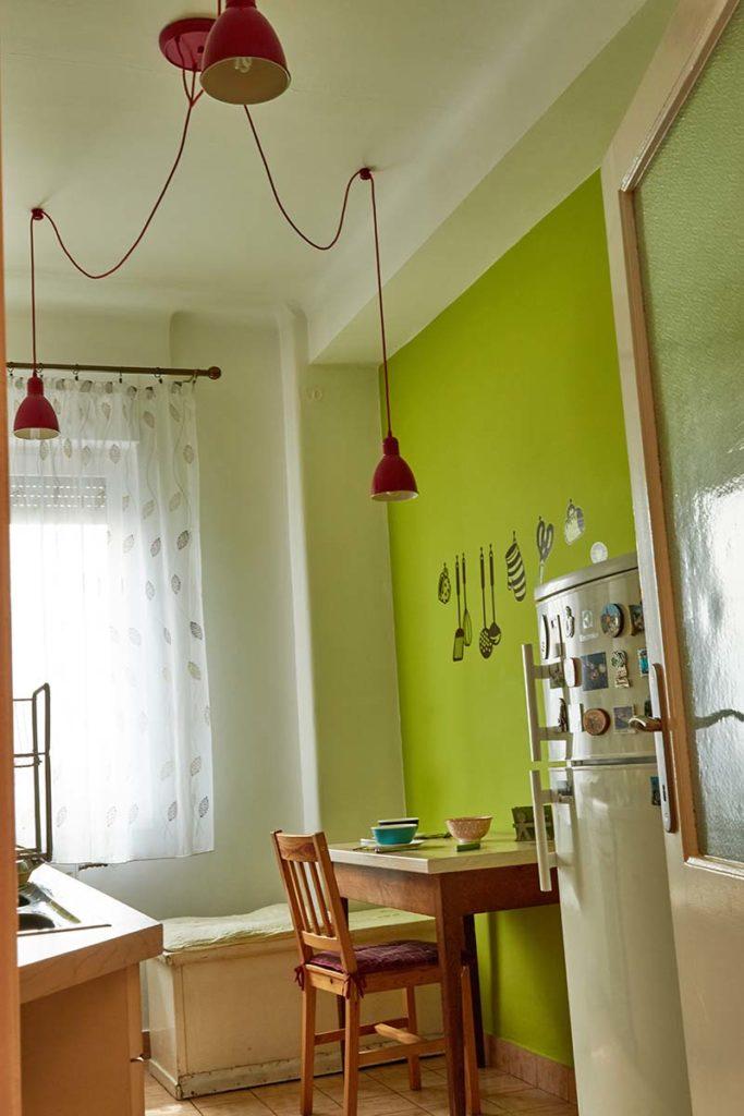 A konyha étkező része látszik a képen. A világos almazöld falat, a piros zsinóron függesztett piros lámpa tagolja és teszi barátságossá.