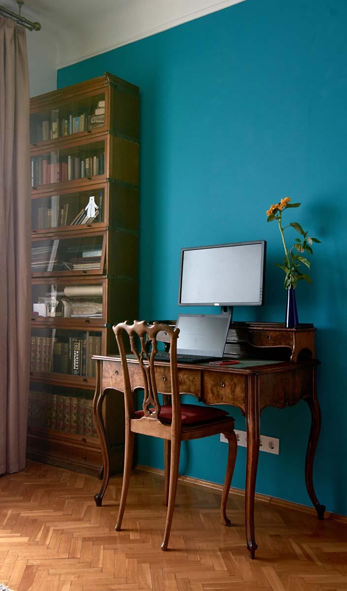 A kanapéval szemközti fal sötét türkizkékre van festve, ami szépen kiemeli az előtte álló régi Lingel üvegezett ajtajú könyvszekrényt és a mellette álló neobarokk íróasztalkát székkel. Nem zavarja a látványt az asztalon elhelyezett laptop, hisz itt munka folyik.