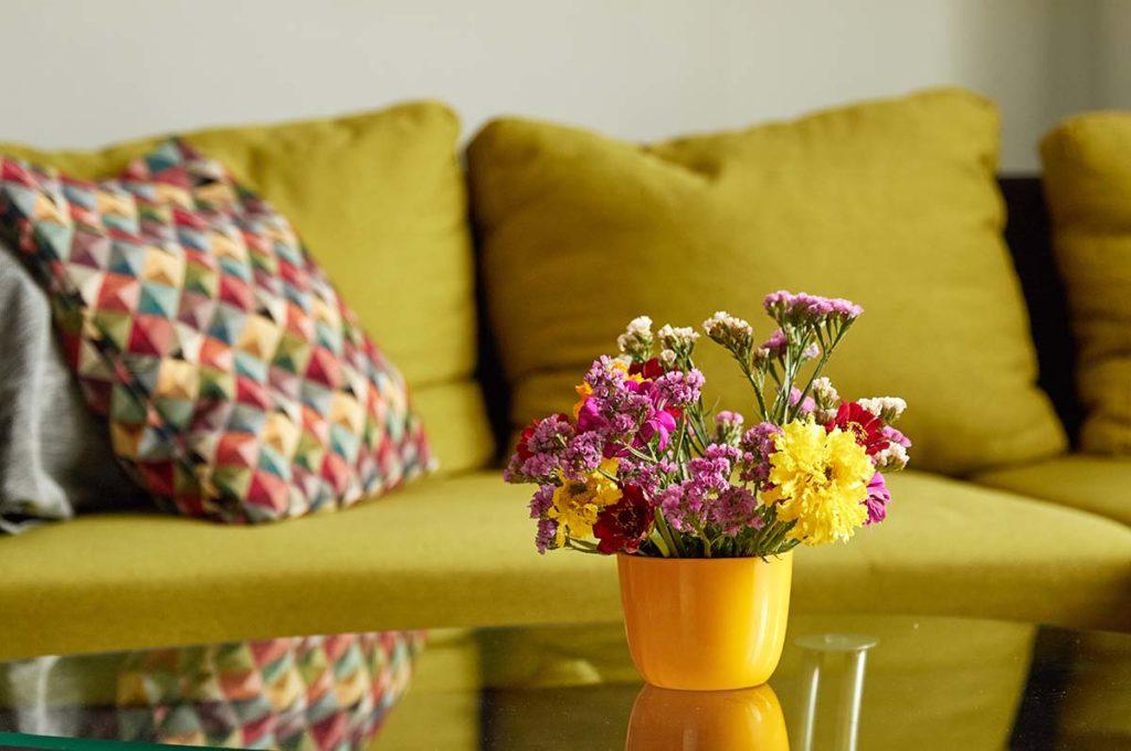Hangulatos csendélet az almazöld kanapé előtti üveglapra heelyzett sárga vázában lévő mezei csokorral.