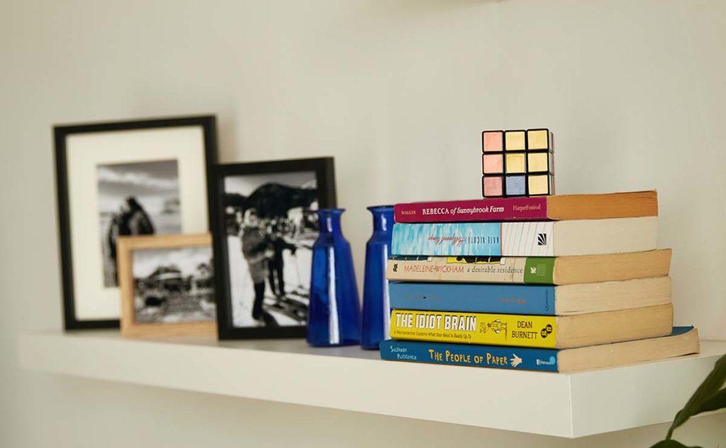 A kanapé fölötti polcin lévő könyvek, dísztárgyaklétszanak