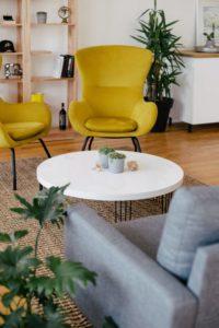 Barátságos nappali részlet beszélgetésre hivogató elrendezéssel, dohányzóasztal fotelekkel, szép színekben, sárga, szürke, fehér.