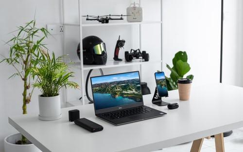 Egy otthoni dolgozó sarok. Fehér fal előtt fehér aztalon egy laptp. Az asztalon is és a padlón is, ami szintén fehér, fehér cserépben kisebb-nagyobb növények. A falon egy polc, amin egy fekete bukósisak.