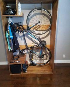 Előszobabútorba épített biciklitároló. Nyers fa színű, nyitott polcos elem.