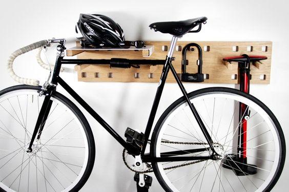 A kerékpártárolás egyik példája. Fehér falra egy natúr fa fogas van szerelve. A fogasra van alasztva a bicikli és a pumpa és egy polc elemmel ,amire egy bukósisak van letéve.