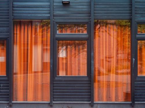 Egy homlokzat részlete egy ablakkal, üvegajtóval. Szép narancssárga függöny látszi az ütca felöl
