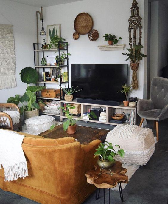 Kényelmes ülőgarnitúra, hangulatos belső puffal, szemben a TV és képek a falon.
