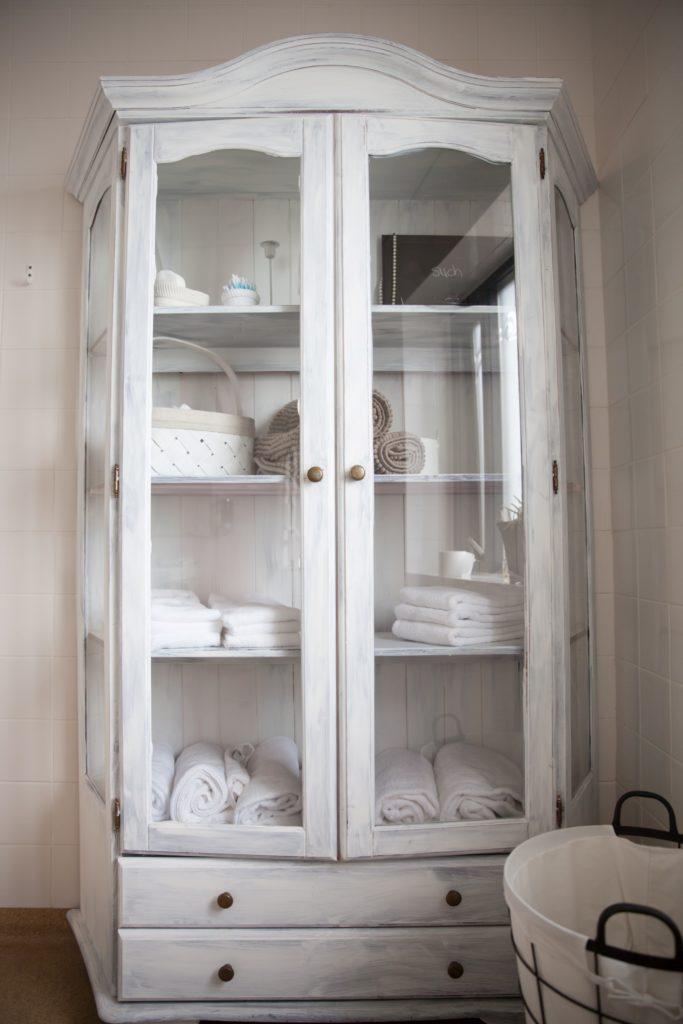 Fehér üvegezett szekrény összehajtott ruhákkak